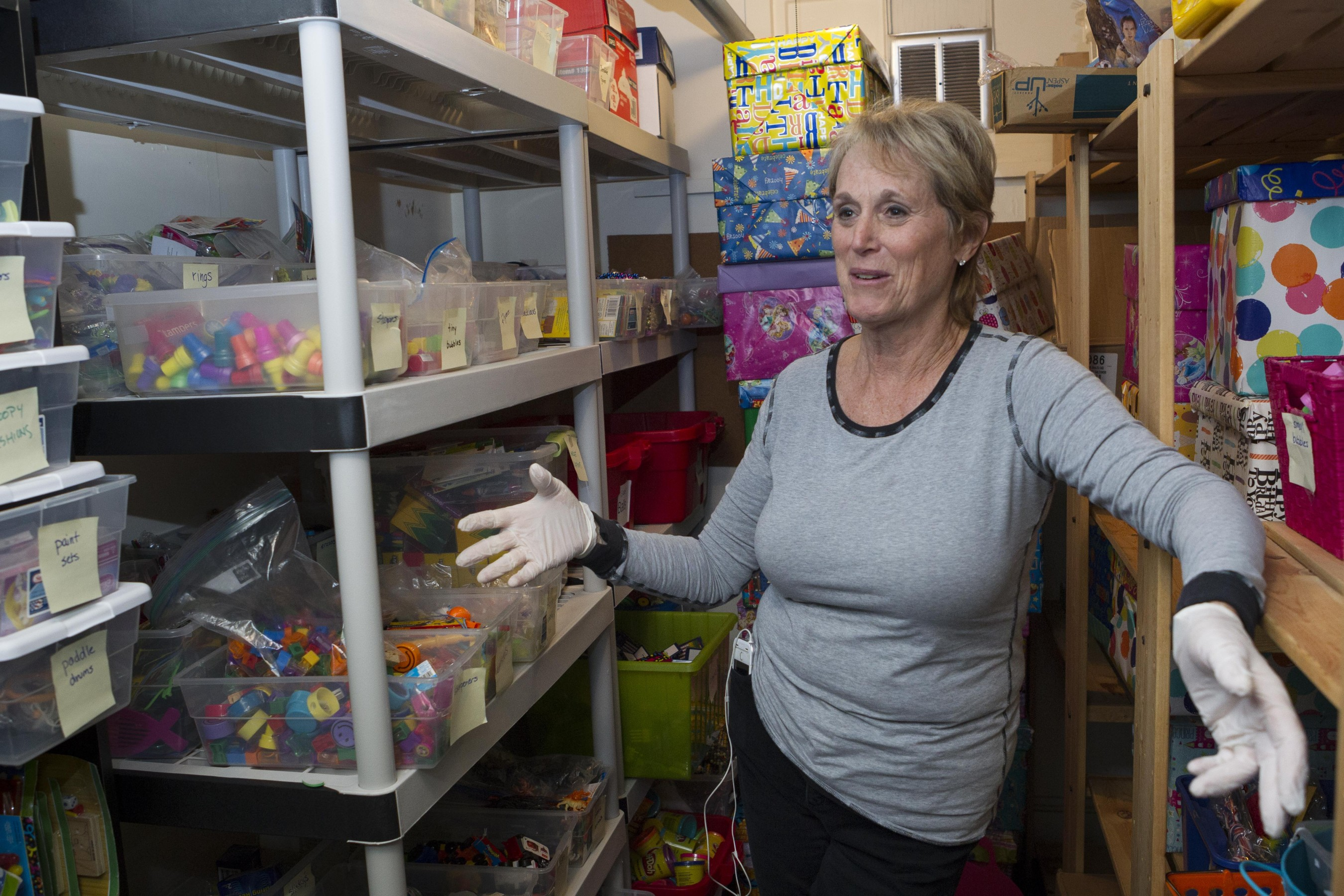 Jill Glazer, a long time Birthday Wishes' volunteer, shows how smaller items for goodie bags are stored at the NGO's main office in Newton, Massachusetts on Wednesday November 18, 2015. Birthday Wishes is a NGO that organizes birthday parties for homeless children in Massachusetts, Rhode Island and Long Island, New York.
