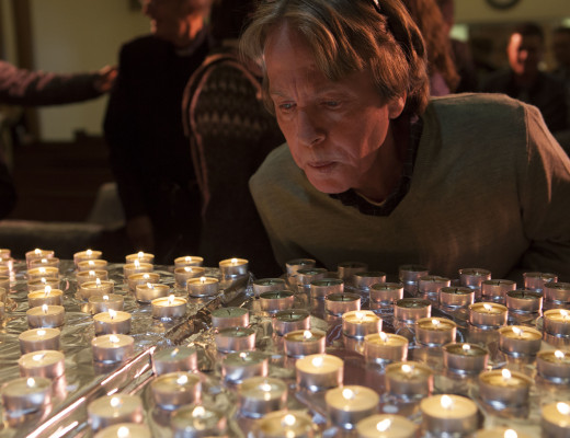 Member of the Church on the Hill blows out candles after the 26th Annual Interfaith Homeless Memorial Service at in Boston, MA on December 21, 2015.